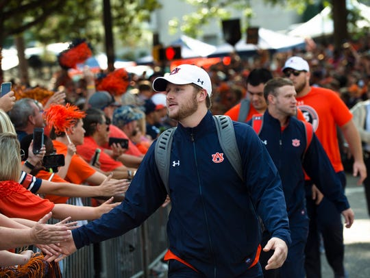 Auburn quarterback Sean White (13) greets fans in Tiger