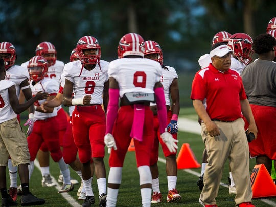 Immokalee High School's football team gets ready on the sideline before a game against Palmetto Ridge last year.