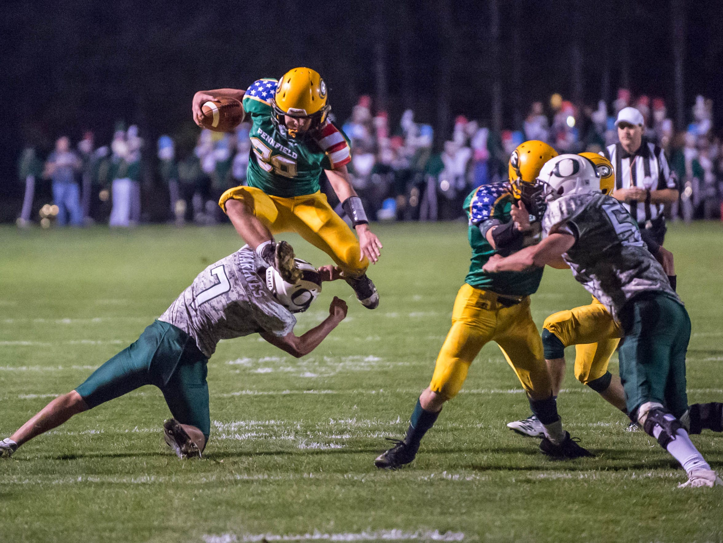 Pennfield's Sam Nichols leaps over the Olivet defender during last year's football season.