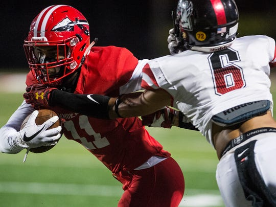 Immokalee High School's Malcom Jackson tries to break a tackle during a game against South Fort Myers High School in Immokalee, Fla., on Friday, Nov. 3, 2017.