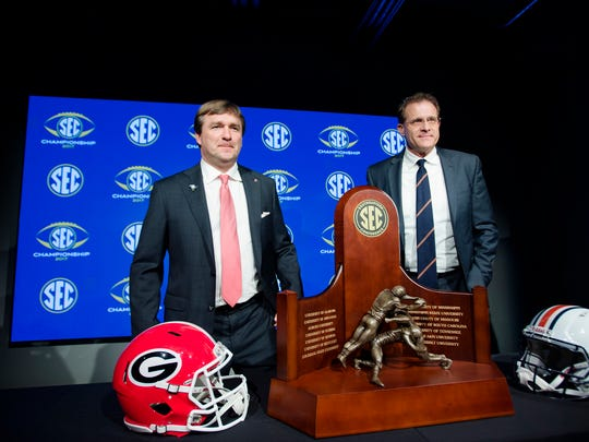 Georgia head coach Kirby Smart, left, and Auburn head coach Gus Malzahn pose infant of the SEC Championship Trophy during the coaches press conference on Friday, Dec. 1, 2017, in Atlanta, Ga.