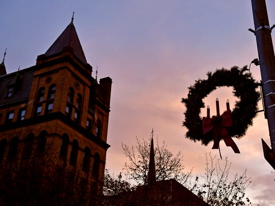 Holiday decorations are silhouetted against a sunset in Continental Square during the expanded, day-long Light Up York festivities Saturday, Dec. 2, 2017, in York. Rather than being held on First Friday evening, as it has in the past, Light Up York was held on Saturday afternoon to encourage families to explore downtown before gathering in Continental Square for the lighting of the Christmas Tree.