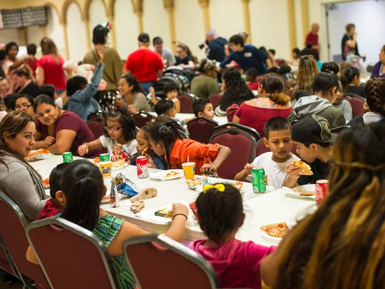 People are seated and begin to eat lunch during the annual Christmas party for economically challenged families in Fort Myers on Saturday, Dec. 16, 2017.