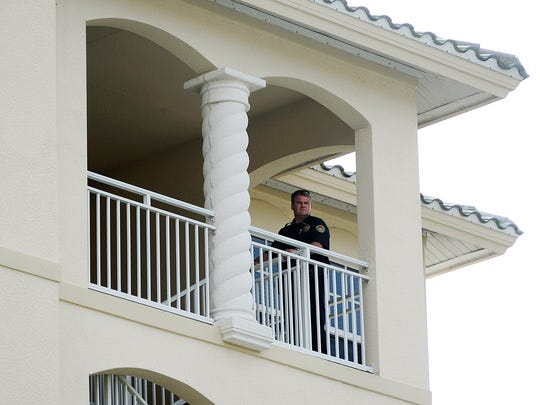 A Marco Island police officer looks over the railing at Park Avenue on Tuesday, Dec. 2, 2014, on Marco Island, Fla. Lisa Troemner, 24, is facing a second-degree murder charge in the killing of Trevor Smith, 30, inside their home in the 800 block of Park Avenue in the Roman Plaza.