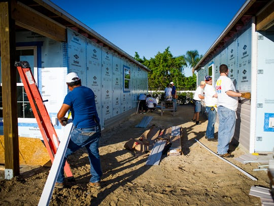 Volunteers put up siding on a house for Habitat for Humanity in Naples on Saturday, Oct 22, 2016.