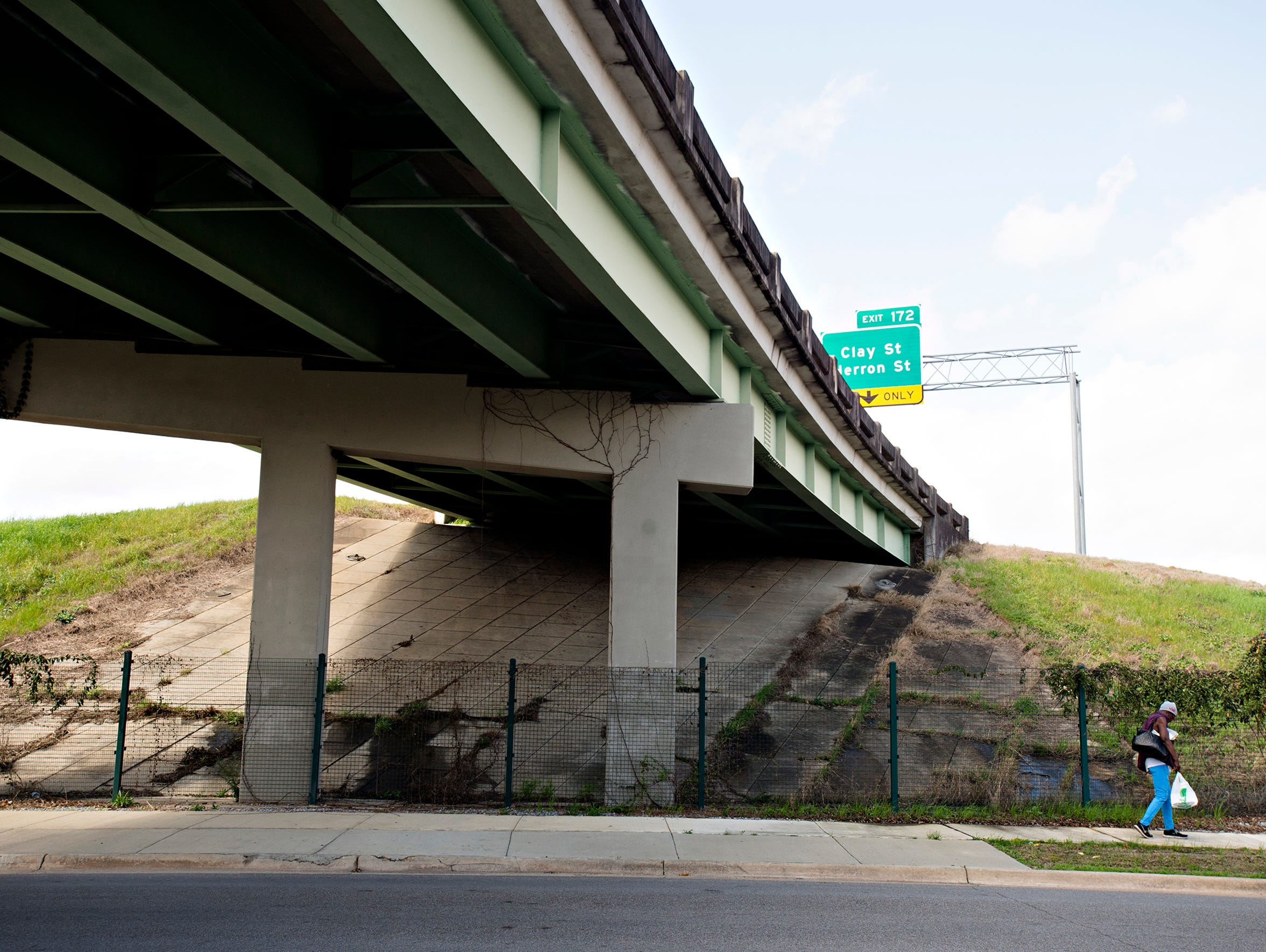 A pedestrian walks under I-85 on Holt Street in Montgomery,