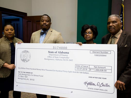 From left, Arica Watkins-Smith, MCBOE board member, Tislam Ellis, Montgomery County Education Association president, Edwin Relf, Child Nutrition Manager at Chisolm Elementary, and Robert Porterfield, MCBOE president, hold a copy of a check during a press conference on Monday, March 12, 2018 at the AEA in Montgomery, Ala., for approximately $1.4 million that was returned to the Montgomery County School System from the State of Alabama in court.