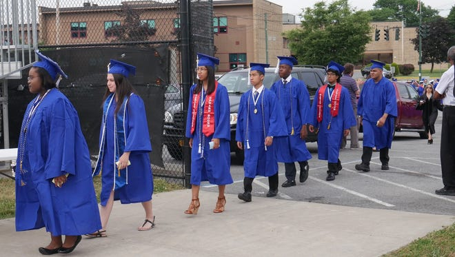 Members of Poughkeepsie High School's class of 2018 walk onto the football field during their graduation ceremony on June 22, 2018.