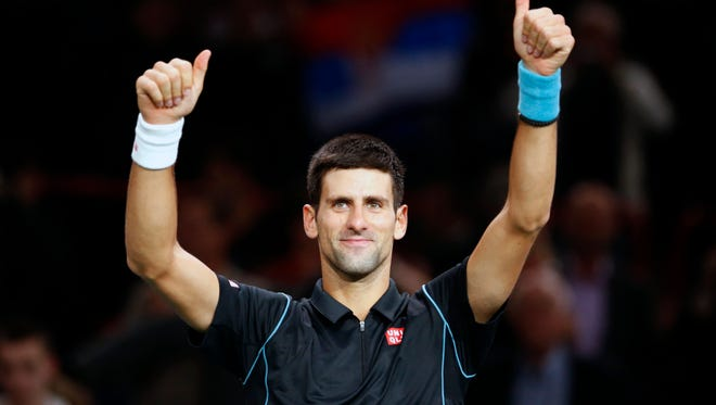 Novak Djokovic of Serbia celebrates after winning against John Isner of the USA during their round of eight match, at the Paris Masters