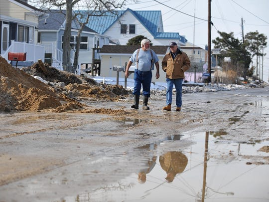 Downe Township Mayor Robert Campbell (right) talks with contractor Bill Erhart, of Vineland, while surveying flood damage on Gandys Beach, Monday, Jan. 25.  Tidal flooding from the weekend's winter storm left the road covered with up to four feet of sand and debris, according to Erhart.