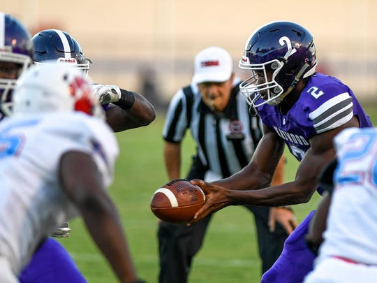 Haywood's Deyondrius Hines passes off the ball to a running back in a TSSAA football game between University School of Jackson (USJ) and Haywood County High School at Haywood High School Stadium in Brownsville, Tenn., on Friday, Aug. 31, 2018.