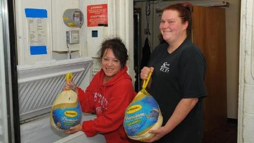 In late 2014, Laurie Viviano (left) and Kimbo Murphy showed off some of the turkeys that were donated for the Sports Venue's annual free Thanksgiving dinner for Garden City senior citizens.