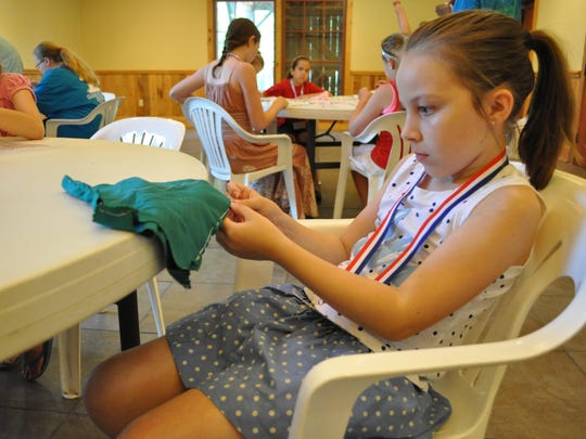 """Jane in June"" campers sew doll clothes on Tuesday morning."