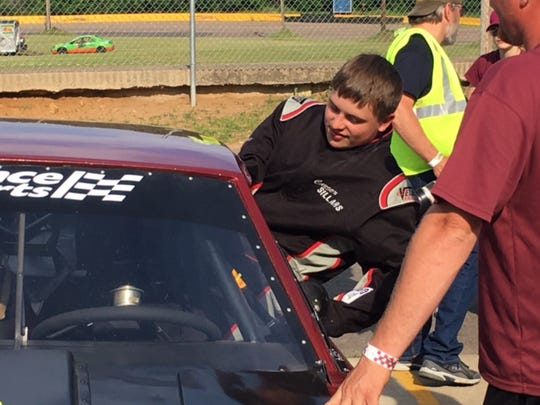Carson Sillars, 15, climbs into his stock car before a heat trial in the Pure Stock Division last Thursday at State Park Speedway in Rib Mountain.