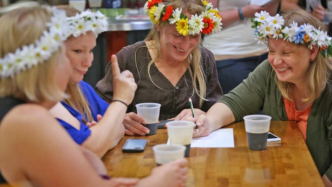 Sandra Kuhn, from left, Ingi Jennings, Whitney Bowman, and Dzintra Tuttle laugh as they figure out answers to trivia questions at the Literary Trivia event at Sun King Brewery, Monday, June 22, 2015. The Indiana Historical Society and the Indianapolis Public Library put on this event for part of an adult reading program. Questions asked included trivia questions about Indiana authors, adult summer reading selections, the Library's McFadden Lecture authors, and Indianapolis Public Library post card photos. These women wore garlands as they visited the brewery to celebrate a Latvian midsummer festival. They joined the trivia contest when they came to the brewery for their own celebration.
