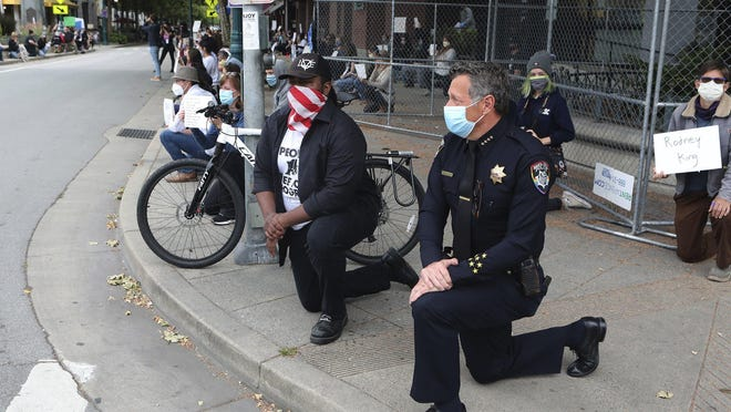 Santa Cruz, Calif., Police Chief Andy Mills, right, and Mayor Justin Cummings, center, take a knee along with hundreds gathered in downtown Santa Cruz on Saturday to honor the memory of George Floyd and bring attention to police violence against black people.