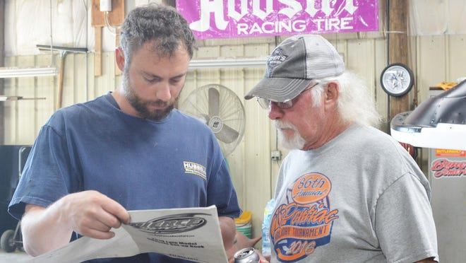 Derek Chandler and his father, Don, look over the setup sheet for their new Bob Pierce race car.