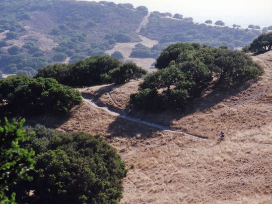A view of Fort Ord National Monument with a lone cyclist on one of the monument's many trails.