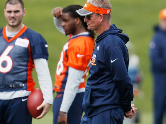 FILE - In this Tuesday, May 23, 2017, file photo, Denver Broncos offensive coordinator Mike McCoy looks on as players take part in an NFL football organized team activities session at the Broncos' headquarters in Englewood, Colo. McCoy, who is returning for his second stint as the Broncos' offensive guru, is tasked with tailoring an offense that clicks with either Trevor Siemian or Paxton Lynch, whichever one may be under center for the first snap of the season ahead. (AP Photo/David Zalubowski, File)