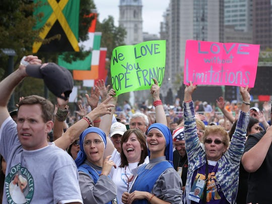 Attendees wave to TV cameras as they wait for the beginning of the mass for the conclusion of the World Meeting of Families on Benjamin Franklin Parkway, Sunday.