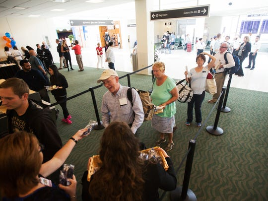 Passengers heading to Cancun board a Sun Country Airlines