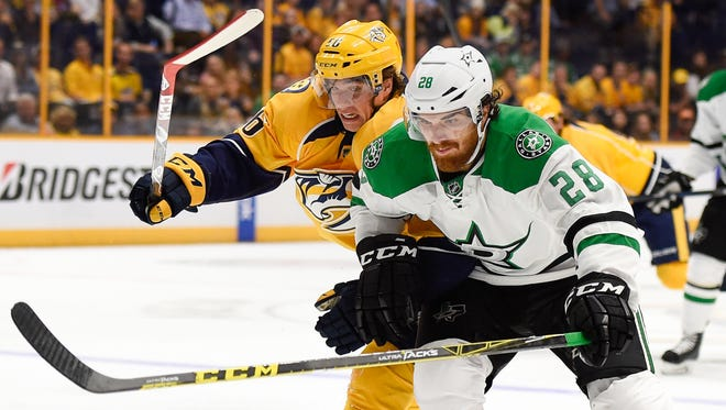 Dallas Stars defenseman Stephen Johns (28) and Nashville Predators left wing Kevin Fiala (56) battle during the first period of an NHL hockey game at Bridgestone Arena, Tuesday, Oct. 18, 2016, in Nashville, Tenn.