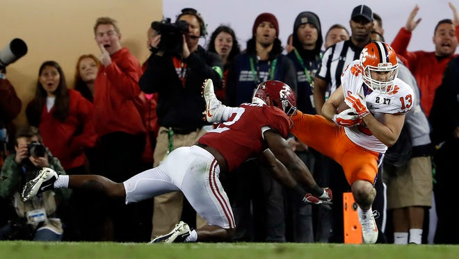 Clemson's Hunter Renfrow, right, catches a touchdown pass in front of Alabama's Tony Brown during the second half of the NCAA college football playoff championship game in Tampa, Fla. Renfrow, a former walk-on, made the catch with 1 second left that gave Clemson a win over Alabama in the College Football Playoff championship game.