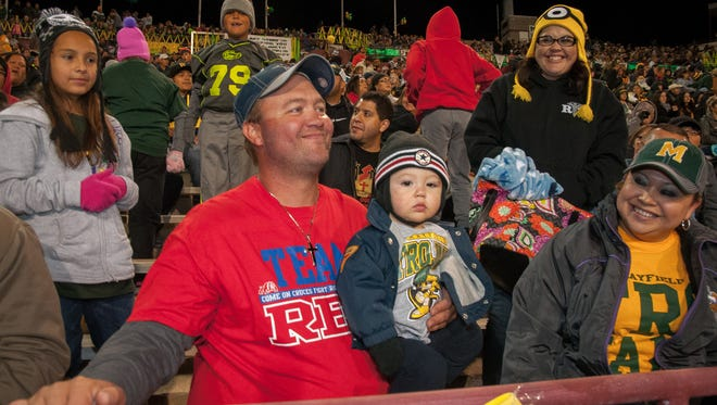 Chris Schmidt, Las Cruces High School Class of 2001, holds his one-year-old son Logan while his wife Tressa Schmidt, Mayfield High School Class of 1999, looks on behind them during the big game between the two schools at Aggie Memorial Stadium on Friday.