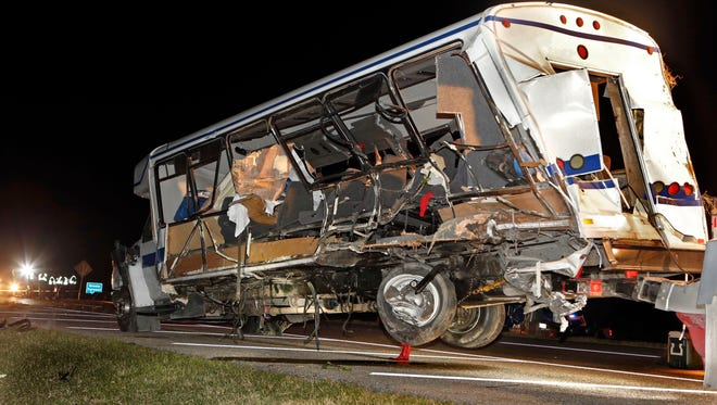 A wrecker removes the team bus as Highway Patrol and emergency personnel work the scene of a fatality accident just south of the Turner Falls area on Saturday, Sept. 27, 2014 in Davis, Okla. Four members of a Texas college softball team died after a tractor trailer crossed over the center median on Interstate 35 and collided with the team's bus Friday night.