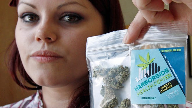 Dani Geen holds a 1 1/2 gram 'care packages' of medical marijuana at the Harborside Health Center in Oakland, Calif.