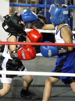 Marcos Moreno, 9, right, lands a punch at James Hammond, 8, during the first bout of the USA Boxing, Inc. Border Boxing Association Junior Olympics boxing event Saturday at the County Coliseum. Moreno won the bout and a trophy.