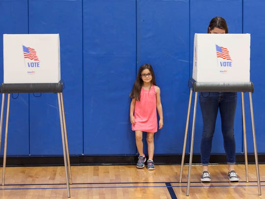 Leah Fail waits as her mother, Keri, casts her ballot