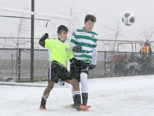 Two players battle the elements Saturday during the 2017 NCAA Men's College Cup Showcase at DE Turf Sports Complex near Frederica.