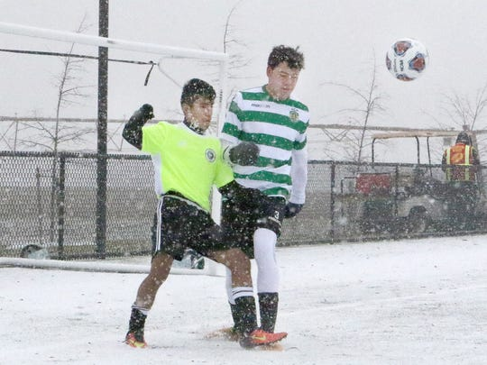Two players battle the elements Saturday during the 2017 NCAA Men's College Cup Showcase at DE Turf Sports Complex in Frederica.