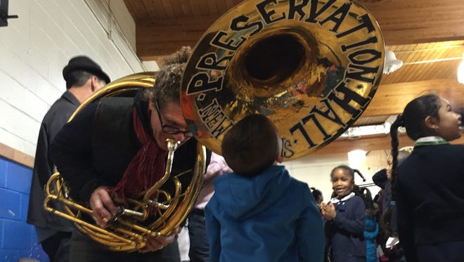 A Hope Academy student looks into a tuba played by Benjamin Jaffee, creative director of the Preservation Hall Jazz Band.