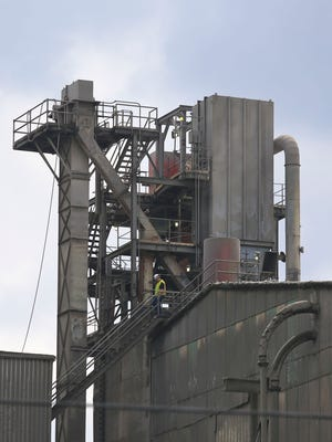 A worker walks down a flight of stairs near an exhaust pipe at the Essroc cement plant in Speed, Ind.