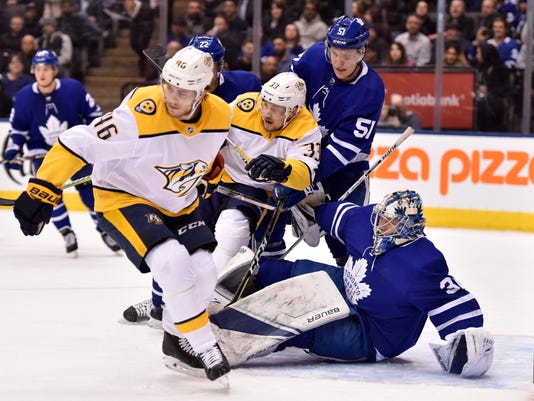 Nashville Predators' Pontus Aberg (46) and Viktor Arvidsson (33) vie for position with Toronto Maple Leafs defenseman Jake Gardiner (51) in front of a fallen Leafs goaltender Frederik Andersen (31) during the first period of an NHL hockey game Wednesday, Feb. 7, 2018, in Toronto. (Frank Gunn/The Canadian Press via AP)