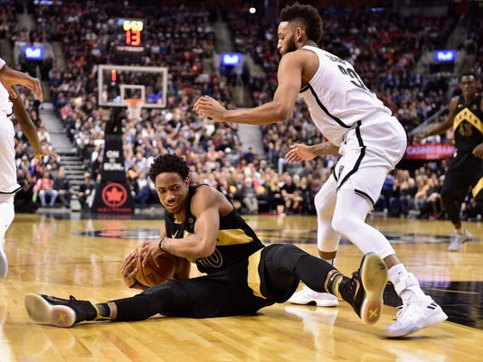 Toronto Raptors guard DeMar DeRozan (10) and Brooklyn Nets guard Allen Crabbe (33) battle for the ball during second-half NBA basketball game action in Toronto on Friday, March 23, 2018. (Frank Gunn/The Canadian Press via AP)