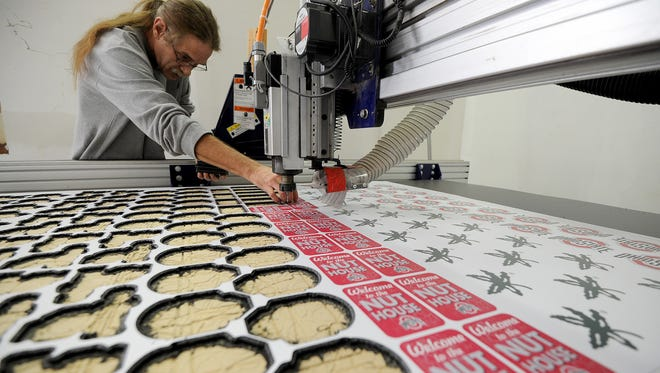 James Baker removes Buckeye decorations cut out on machine Monday afternoon at Spazz Monkey in Ontario.