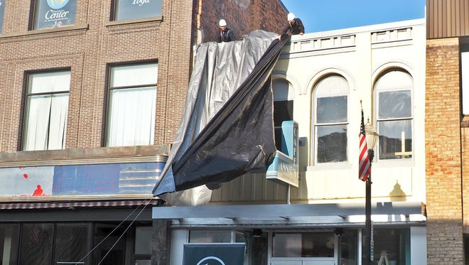 Lt. Gov. Rebecca Kleefisch counts down from ten on a megaphone as workers pull back the silver tarp which had disguised the new facade of Annie's Fountain City Cafe, on Wednesday.