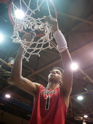 New Albany Bulldogs guard-forward Romeo Langford cuts down the championship net following his team's 84-70 win against Evansville Reich in the Indiana High School Athletic Association Boys Seymour Regional .