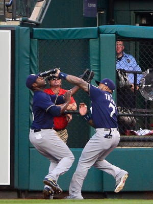 Brewers outfielders Lorenzo Cain (left) and Eric Thames collide when going after a fly ball in the first inning.