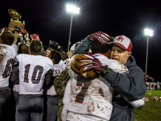 Port Huron's DeAngielo Sanderson Jr hugs coach Ryan Mullins after beating Port Huron Northern in the Crosstown Showdown Friday, Oct. 21, 2016 at Memorial Stadium in Port Huron.
