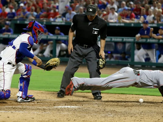 Cincinnati Reds Brandon Phillips, right, scores against Texas Rangers catcher Robinson Chirinos as home plate umpire Larry Vanover watches during the seventh inning of a baseball game in Arlington, Texas, Tuesday, June 21, 2016. The Reds won 8-2. (AP Photo/LM Otero)