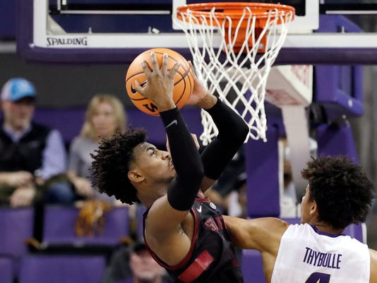 Stanford's Daejon Davis, left, grabs a rebound in front of Washington's Matisse Thybulle in the second half of an NCAA college basketball game Saturday, Jan. 13, 2018, in Seattle. (AP Photo/Elaine Thompson)