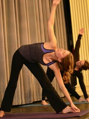 Allie Harris, 23, of Essex, front, practices yoga with