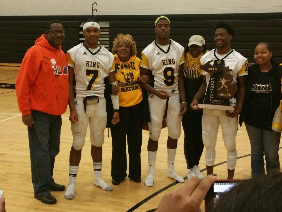 Detroit King's Armani Posey (7), Donnie Corley (9) and Lavert Hill (21) pose with family members and the state championship trophy.