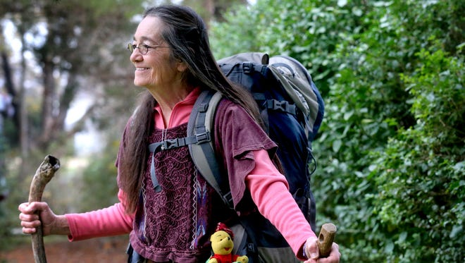 Winnie Hardy, who is 67, hiked the entire Appalachian Trail in about eight months. Hardy stands in her backyard  on Wednesday, Dec. 9, 2015, with her faithful trail partner, Winnie the Pooh, who rode on Hardy's backpack the entire trip.