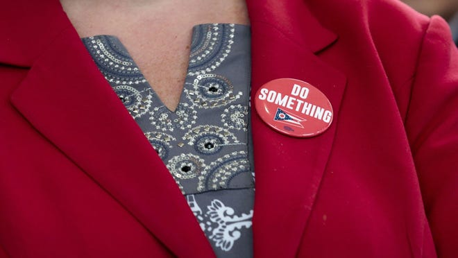 """Wearing a button with the phrease """"Do Something,"""" Dayton Mayor Nan Whaley waits to speak during a press conference unveiling the STRONG Ohio Bill on Monday, October 7, 2019 at the Ohio Department of Public Safety in Columbus."""