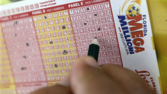 A customer fills out a Mega Millions ticket at a store in Hialeah, Fla. Tuesday's Mega Millions drawing will give lottery players a shot at the 10th largest jackpot in U.S. history. (